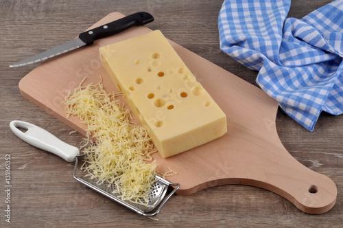 Emmental sur une planche à découper avec une râpe à fromage et de l'emmental râpé