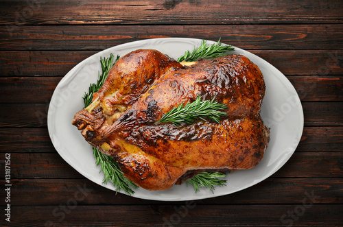 Fotografia Roasted duck with rosemary on plate on black background