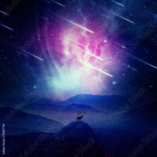 Photo  Majestic deer with long horns as tree branches stand on the peak of a rocky valley below a wonderful night sky with falling stars and sparkles