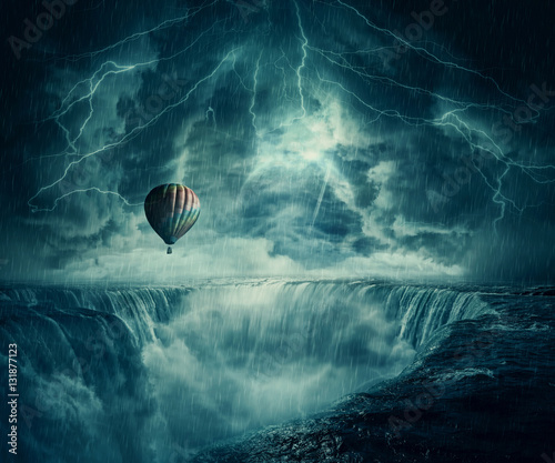 Photo StormFall Inspirational imaginary view, scary landscape as a hot air balloon fly over the chasm of a foggy waterfall below a dark stormy sky
