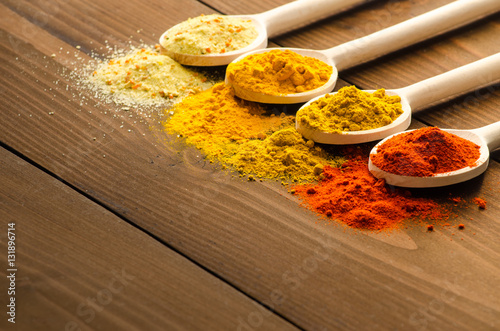 Spilled powder spices and wooden spoons Wallpaper Mural