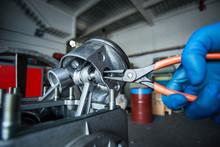 Mechanic Fixing A Compressor Engine