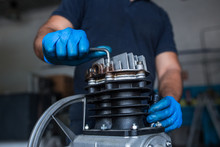 Mechanic Fixing A Compressor E...