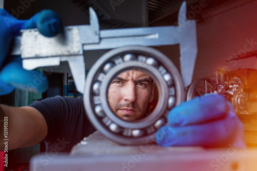Close up of mechanic using a vernier caliper to measure a ball bearing
