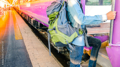 Fotografie, Obraz  Traveler holding and stepping up to a train with backpack for journey travel at train station