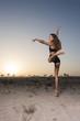 beautiful girl in desert sunrise jumping