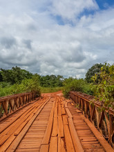 Dodgy Wooden Bridge With Timber Planks And Old Iron Rails Crossing River In Gabon, Central Africa