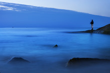 Fishing Man Standing On Rock With Blue Blur Sea Water At Dawn