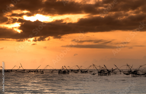 Poster Marron chocolat Silhouette of traditional fishing method using a bamboo square dip net with sunrise sky background,livelihoods of fishermen at Pakpra, Phattalung in Thailand