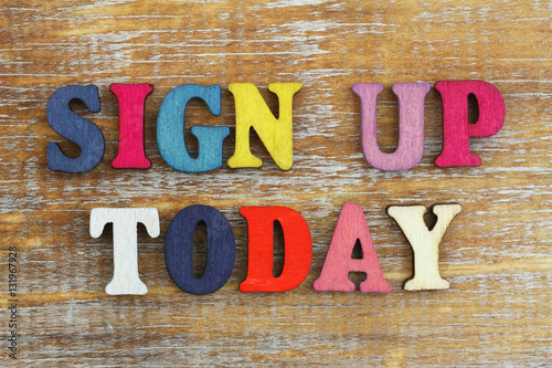 Fotomural  Sign up today written with colorful letters on rustic wooden surface