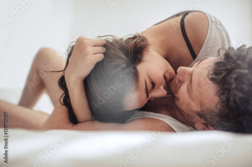 Young couple caressing in bed