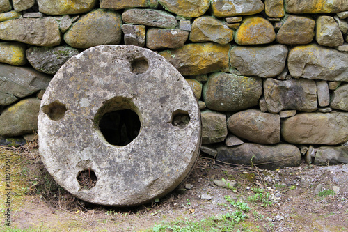 Photo  Old millstone on a background of stone wall, Etera, Bulgaria