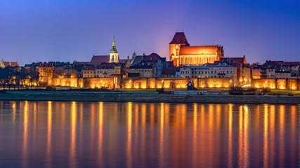 Fototapeta Torun at night, medieval Old Town reflected in Vistula river, Poland. Europe.
