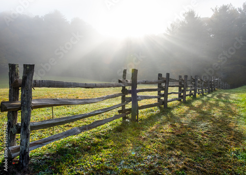 Fotografie, Obraz  Sun Rays in Foggy Field and Split Rail Fence