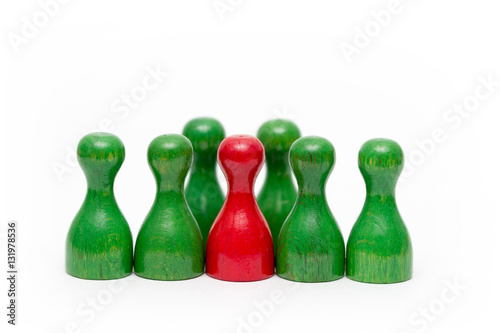 Fotografía  rote Spielfigur aus Holz zwischen grünen Spielfiguren isoliert
