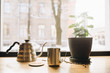 The window and windowsill with pitcher, coffee, green flower in daylight mear