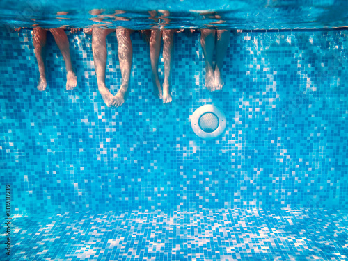 Children's and adults legs underwater in swimming pool Fototapeta