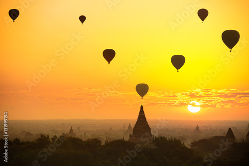 Poster Jaune Beautiful sunrise and hot air balloons over ancient pagoda in Bagan is old kingdom in past, Myanmar