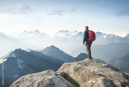 Fototapeta Tourist on the peak of high rocks. Sport and active life concept.. obraz