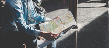 Traveler Sitting And Looking In Map For Waiting Train At Train Station. Travel Concept By Train With Vintage Tone.
