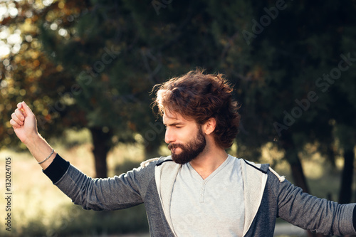 Young satisfied man in forest portrait  Happy pleased guy