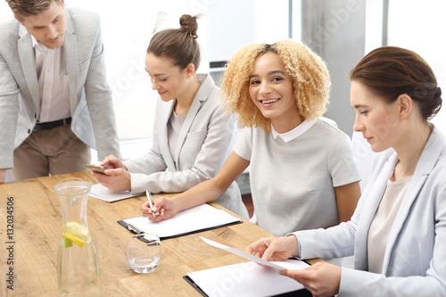 Fototapeta Zespół pracowników podczas pracy.Grupa młodych pracowników na spotkaniu firmowym w sali konferencyjnej obraz