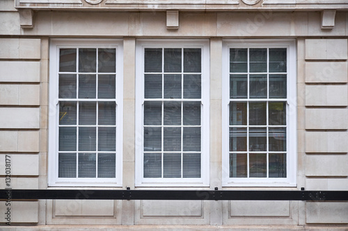 Photo Window section with three colonial style windows in sand colored ashlar walling