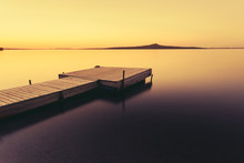 Wooden Pier On A Blue Lake Sunset And Smooth Reflection On Water. Long Exposure, Zerendi Lake, Kazakhstan.