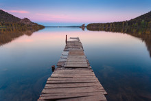 Wooden Pier On A Blue Lake Sunset And Smooth Reflection On Water. Long Exposure; Borovoye Lake; Kazakhstan.