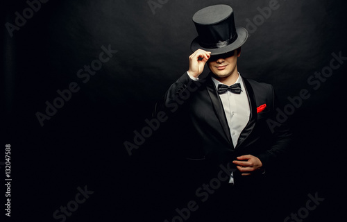 Fotografie, Obraz  A magician in a black suit holding an empty top hat and magic wand isolated on b