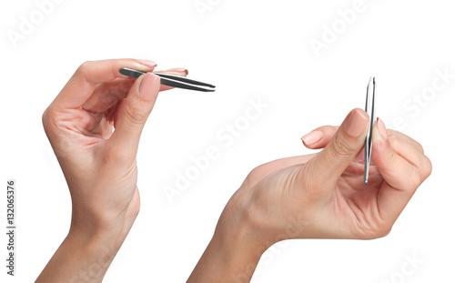 Fotografía  Girl makeup artist holds in both hands two metal, steel tweezers for plucking eyebrows