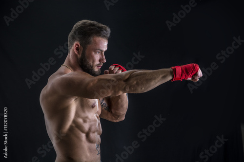 Photo  Young handsome topless boxer in red gloves looking at camera on black studio