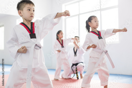 Canvas Print Young instructor teaching children taekwondo in studio