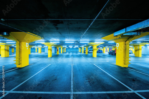 Underground garage parking lot with few cars and empty spaces Plakát