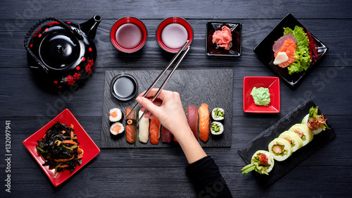 Pinturas sobre lienzo  Woman eating sushi with chopsticks top view