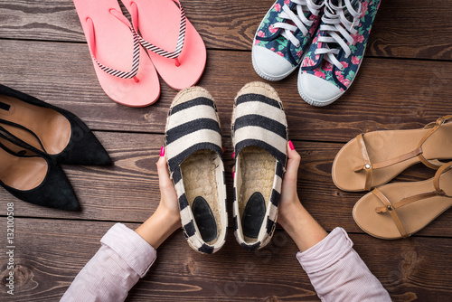 Female shoes collection on wooden table with woman's hands holding pair of shoes