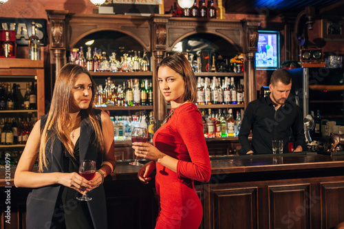 Photo  Two attractive young women meeting up in a pub for glass of red wine sitting at