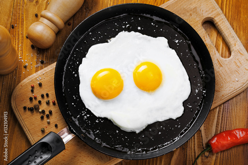 Foto op Plexiglas Gebakken Eieren Fried eggs for delicious healthy easy breakfast on a table. Fresh homemade meal on a frying pan. Traditional breakfast food. International cuisine food. Top view.