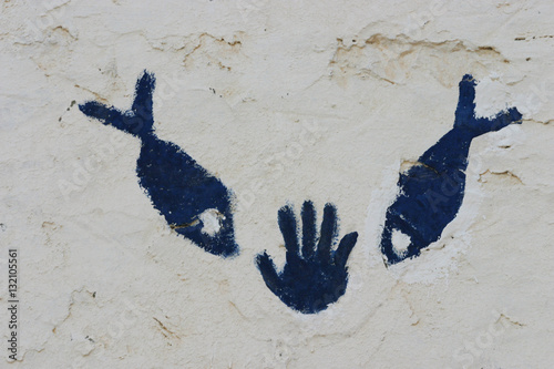 Photo  Hand and fish symbol on the wall in the sahara Tunisia