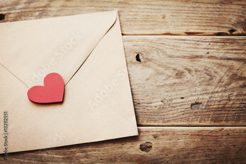 Photographie  Envelope or letter and red heart on vintage wooden table for love message on Valentines Day in retro toning
