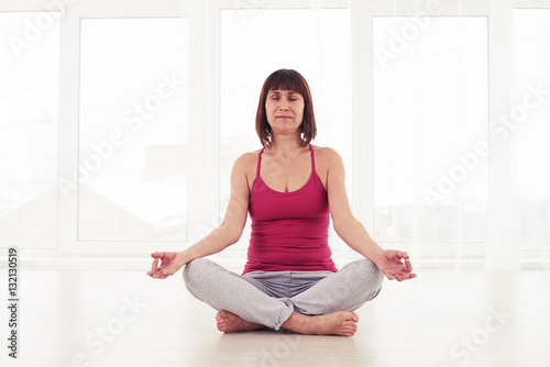 Fotobehang School de yoga Portrait of delicately-built woman sitting in lotus pose and med