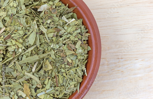 Fotografia  Bowl filled with cut and sifted senna leaf top close view atop a wood table