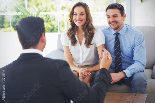 Smiling couple in meeting with a financial adviser Canvas Print