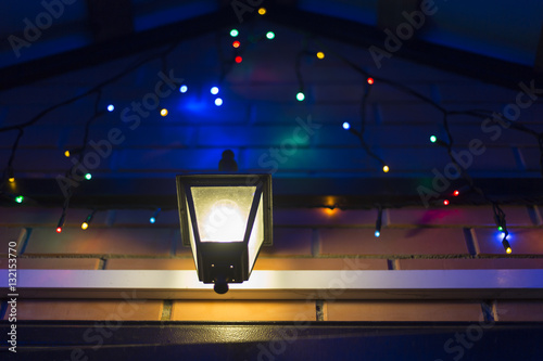 Colorful Christmas Lights On House.Glowing Colorful Christmas Lights And Lamp At The House