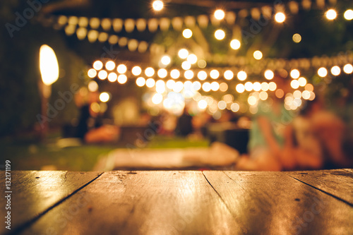 Obraz Image of wooden table in front of abstract blurred restaurant lights background - fototapety do salonu