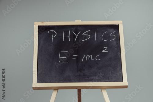 Physics word and formula E=mc2 on chalkboard Poster