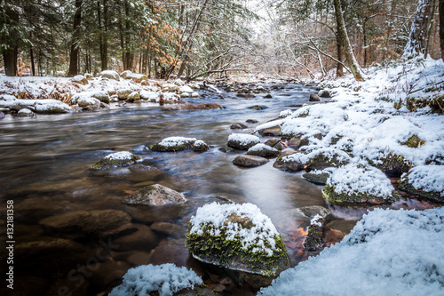 Winter river scene flowing among snowy rocks