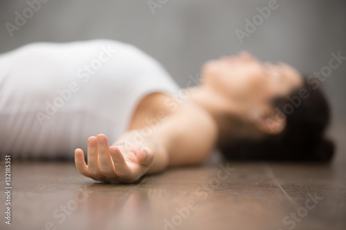 Obraz na plátně Beautiful young woman working out on wooden floor, resting after doing yoga exercises, lying in Shavasana Corpse or Dead Body Posture , relaxing