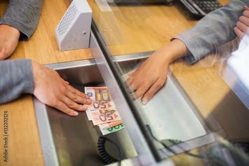 Fotografía  clerk giving cash money to customer at bank office