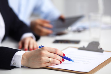 Businesswoman sitting in office, writing on documents